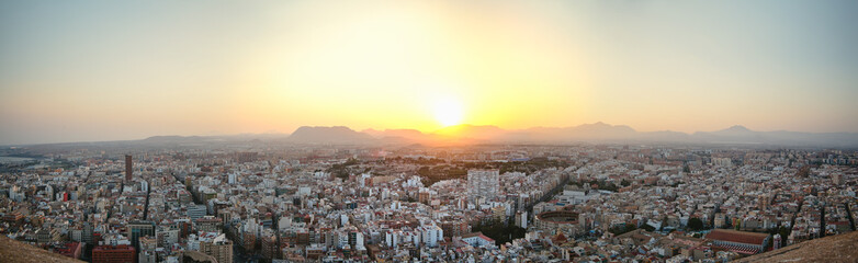 Panoramic view of the old town of Alicante, backlit at sunset from the top of the castle of Santa Barbara