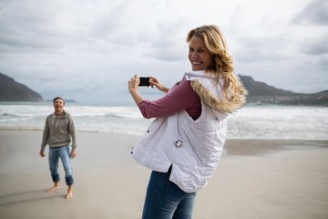 Portrait of mature woman clicking a picture of man