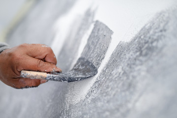 hand of worker use brush for color paint concrete Loft style on wall