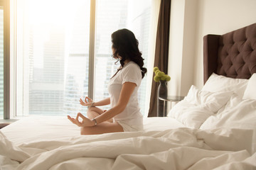 Young sporty woman practicing yoga at home bedroom after waking up, sitting on unmade bed in Padmasana exercise, Half Lotus pose on meditation session, working out wearing white casual clothes, indoor