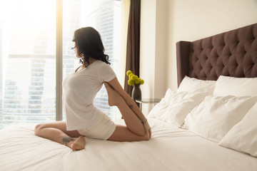 Young attractive woman practicing yoga after waking up, sitting in One Legged King Pigeon exercise, Eka Pada Rajakapotasana pose working out, wearing white casual clothes, indoor full length, bedroom