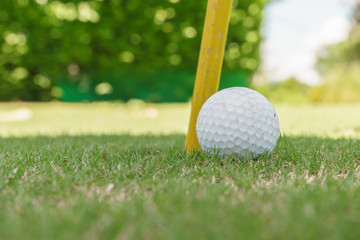 close up golf ball beside the hole