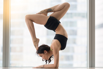 Young attractive woman practicing yoga, standing in variation of Pincha Mayurasana exercise, working out, wearing sportswear, black tank top, shorts, indoor full length, floor window with city view