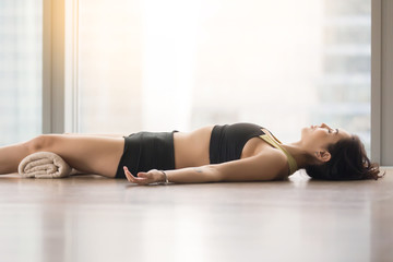 Young attractive woman practicing yoga, lying in Corpse, Dead Body exercise, Savasana pose, working out, wearing sportswear, black tank top, shorts, indoor, near floor window with city view