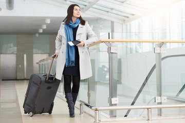 Airport business woman with smart phone at gate waiting in terminal