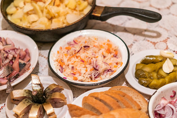 Country dinner with roast potatoes, smoked fish, pickles, bread and coleslaw