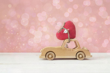 Wooden toy car with heart on the roof on a pink background. Plac