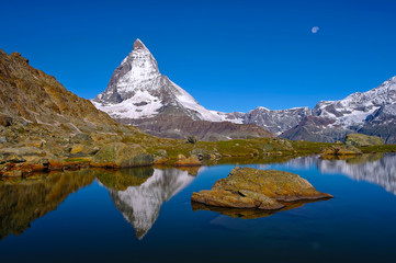 Poster de jardin Reflexion Scenic view of Matterhorn peak covered by snow reflected in surface lake water