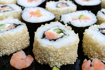 Traditional eastern dish with salmon sushi rolls on a black plate.