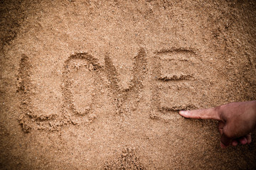 Man writing text in the sand on beach, Valentine's concept.