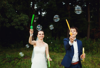 the groom and his wife make soap bubbles
