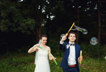 funny  groom and his wife make soap bubbles