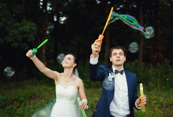 the couple produces bubbles outdoors