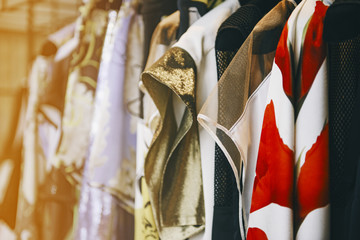 Wall Mural - Colorful clothes on hangers in a luxury fashion store with backlight effect.
