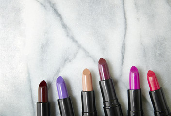 A selection of colorful lipstick make up arranged on a white marble counter background with blank space above