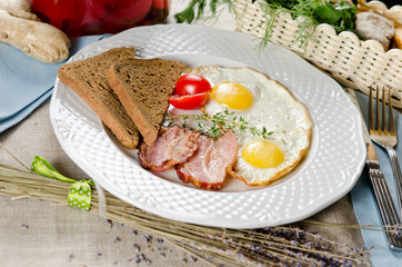 Hearty breakfast. Fried eggs with bacon, rye bread and cherry to
