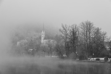 Church among the trees surrounded by fog near lake Bled, Slovenia. Black and white