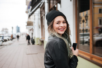 Cheerful young woman listening music with earphones.