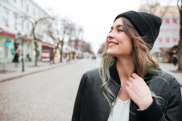 Smiling young lady wearing hat walking on the street