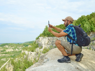 Man tourist uses tablet computer sitting on edge of cliff in mou
