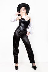 sexy woman with hourglass figure dressed in black leather corset and pants with wide-brimmed hat
