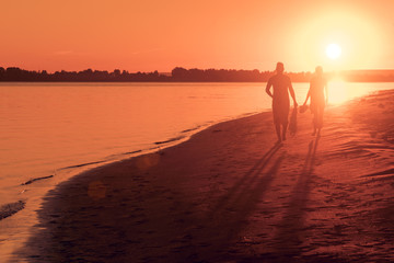 Couple walks along the beach at sunset