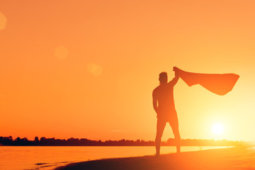 Silhouette of a naked man with a towel on the beach at sunset