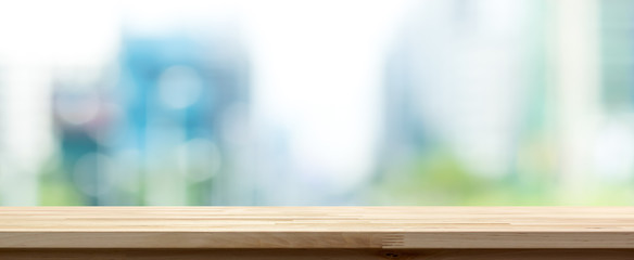 Wood table top on blur buildings in the city background, panoramic banner Wall mural