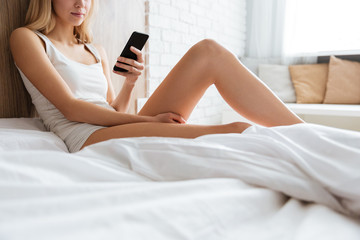 Cropped image of woman on bed with phone