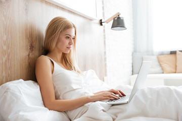Side view of woman on bed with laptop