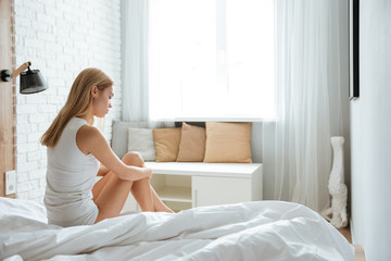 Pensive depressed young woman sitting and thinking on bed