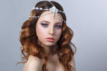 Beauty portrait elegant bride with beautiful makeup and curls in tiara isolated on a gray background.