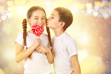 Boy kisses little girl with candy red lollipop in heart shape. Valentine's day art portrait