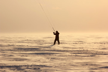 Kite surfer on snowboard background at sunset. Snowkiting in the snow on frozen lake.