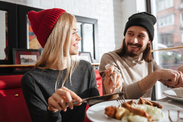 Side view of smiling couple eating in cafe