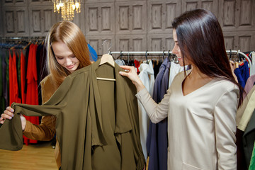 Two Women shopping choosing dresses. Beautiful young shoppers in clothing store.Shopping concept. Sale.