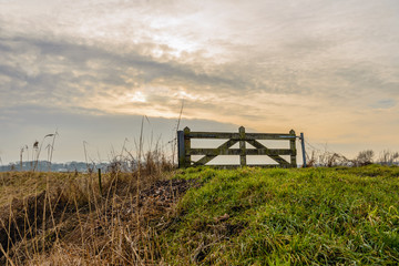 Closed wooden gate on top of Dutch dike