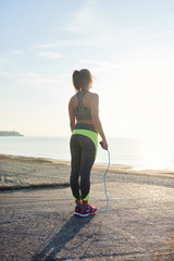 Sportswoman with jumping rope looking at sunny seascape.