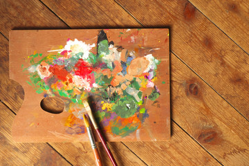 Palette and paintbrushes on wood background