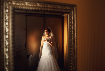 bride in a white dress standing near  the cabinet
