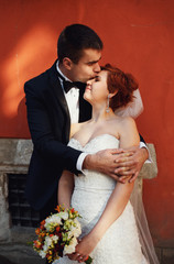 young couple standing near the orange wall and kiss