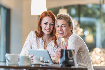 a mother and her daughter sit in a cafe using a tablet