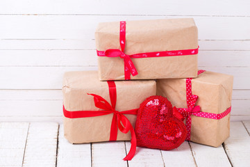Gift boxes and red decorative heart  on white wooden background.