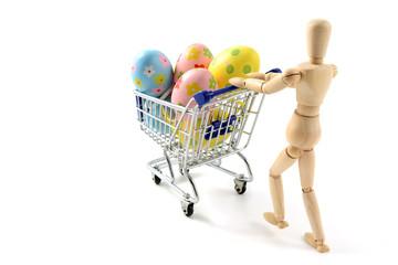 wooden mannequin shopping easter eggs in shopping cart on white