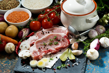 two pieces of raw pork and fresh ingredients for preparation