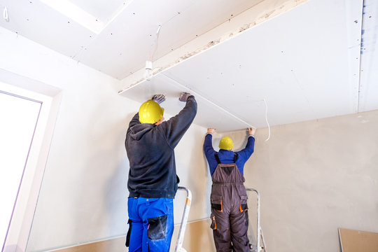 Workers assemble a suspended ceiling with drywall