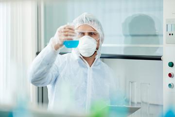 Chemist studying biohazard fluid in tube