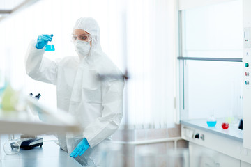 Pharmacologist in protective overalls looking at dangerous toxic fluid