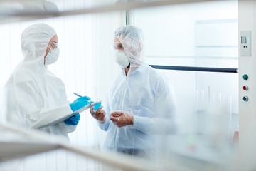 Two contemporary scientists in protective uniform working in chemical laboratory