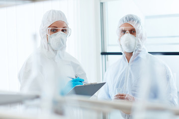Two colleagues in overalls, eyeglasses, gloves and respirators working in lab